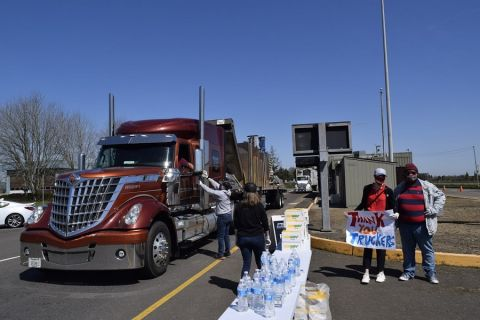 Drivers receive food and water at a Meals for Drivers event, hosted by the Oregon Trucking Associations