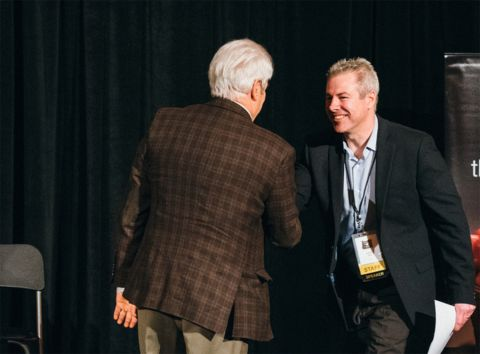 Aaron Fox (right) is greeted by outgoing OMEP president Chris Scherer during the Oregon Manufacturers Summit.