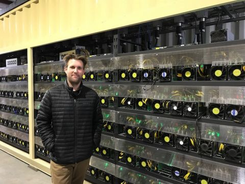 OregonMines CEO Terrence Thurber in front of cryptocurrency mining machines at his facility in The Dalles